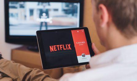 Muž se dívá na tabletu na Netflix.